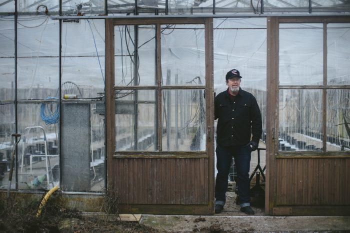 Mark Wilcox står vid ingången till ett växthus